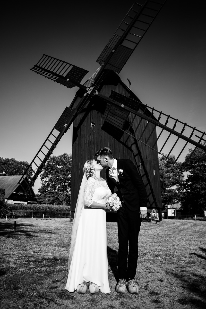 Hochzeitspaar in Holzpantoffeln küsst sich vor einer alten Holz