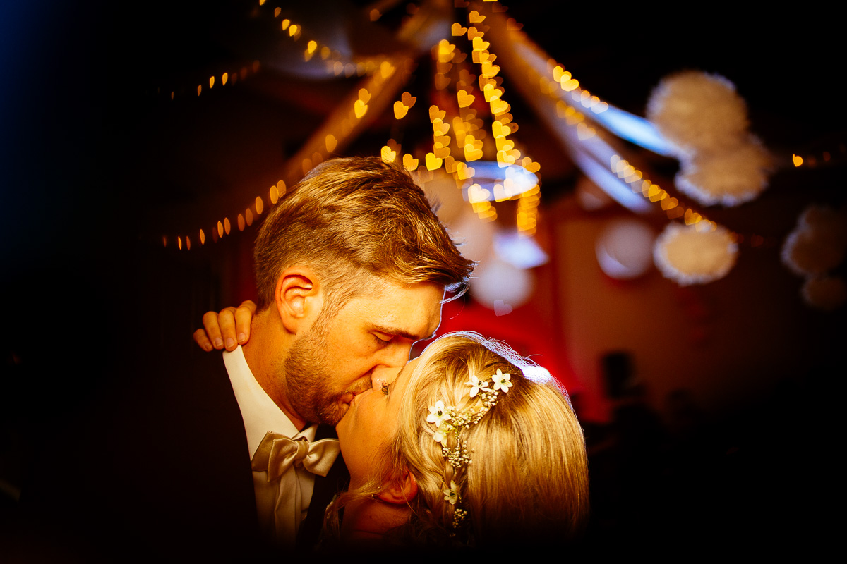 Brautpaar küsst sich unter Lichtern in Herzform