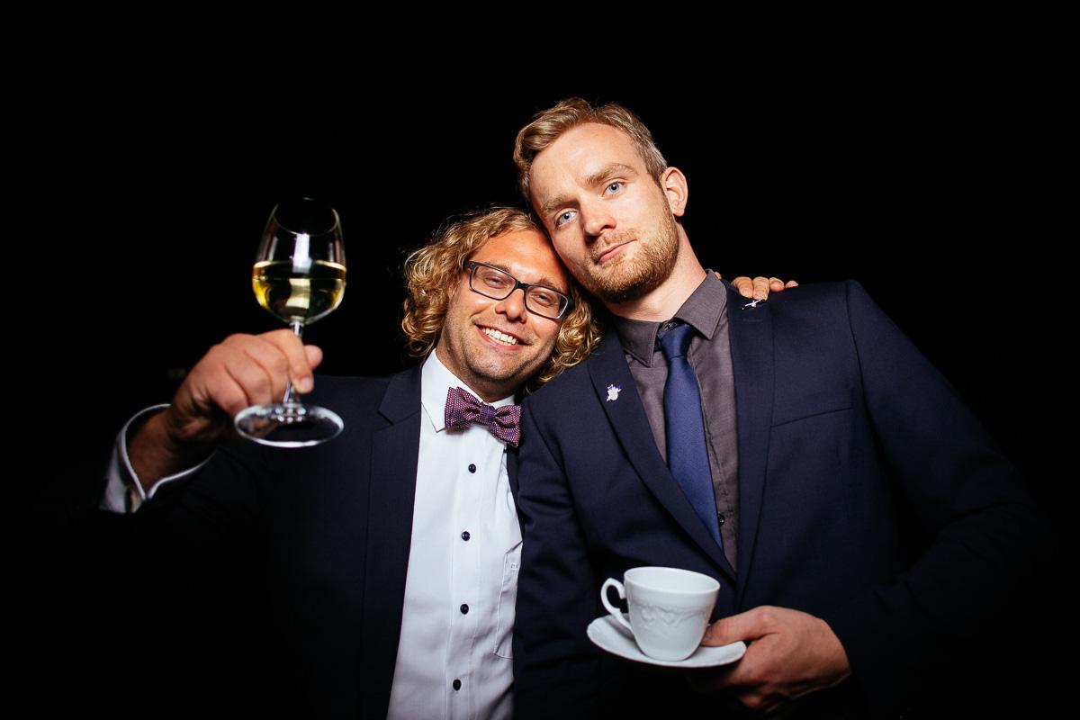 Gäste posieren mit Wein und Kaffe vor der Photobooth
