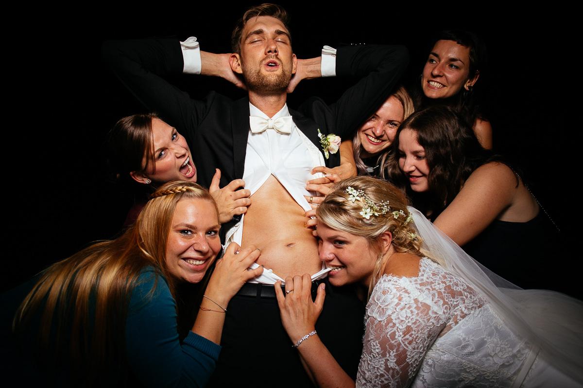 Mädchen und Braut fallen über den Bräutigam her