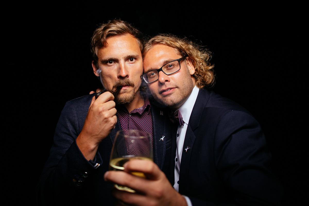 Gäste posieren mit Wein und Pfeife vor der Photobooth