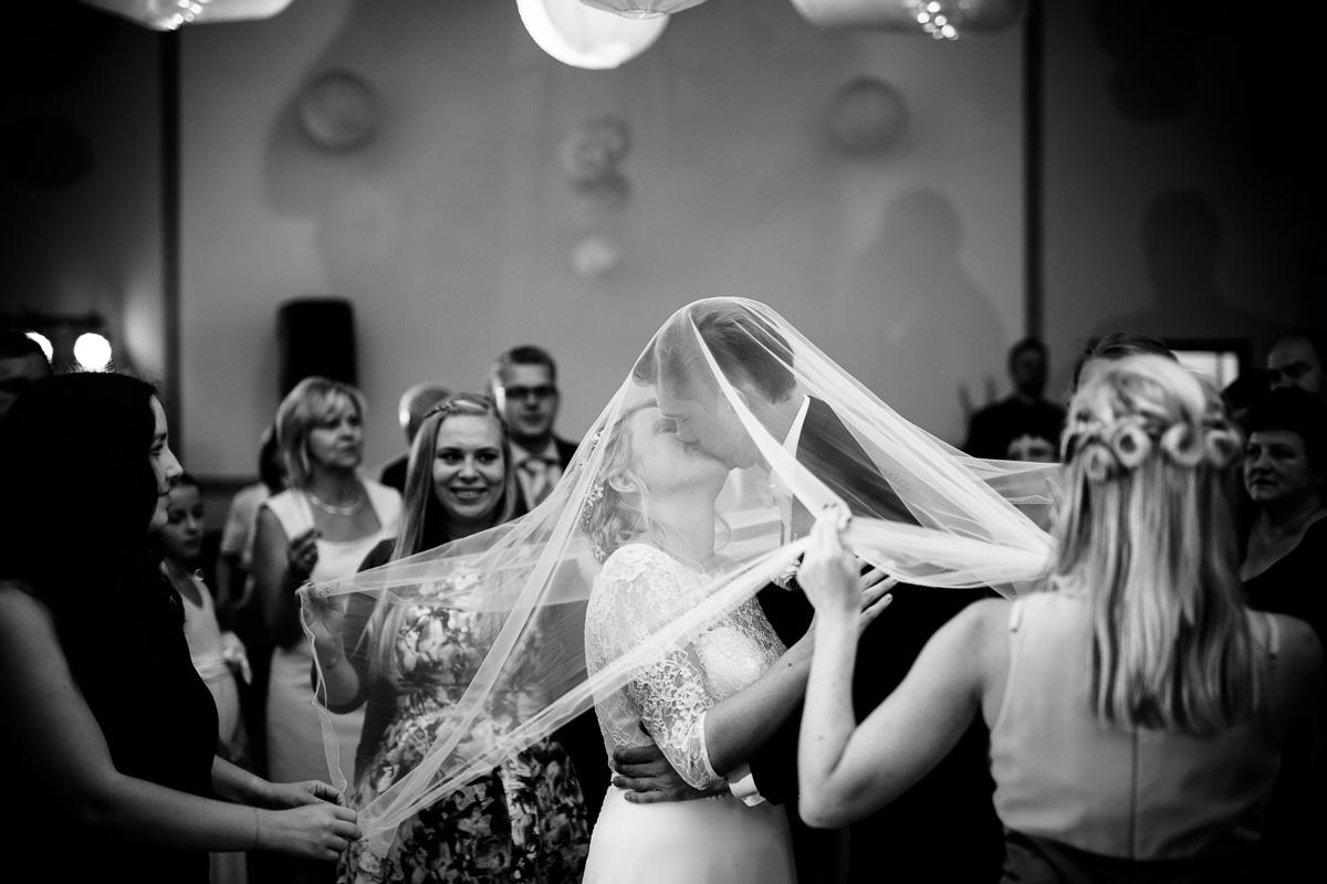 Brautpaar küsst sich unter dem Brautschleier