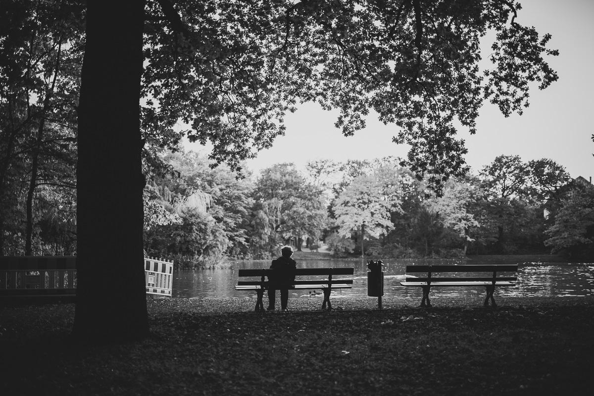 Frau sitzt auf Parkbank vor einem See