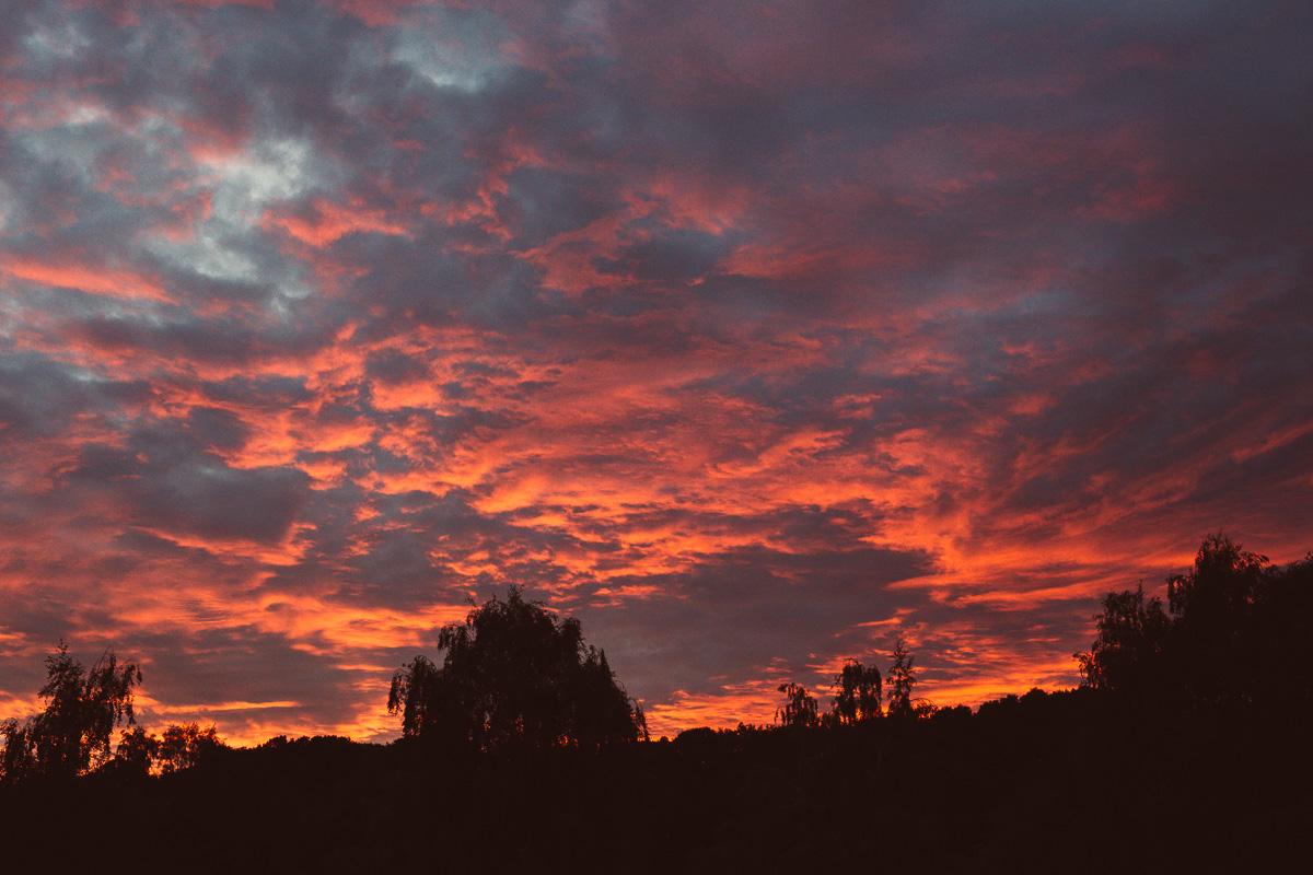 Wolken werden von der untergehenden Sonne rot angeleuchtet