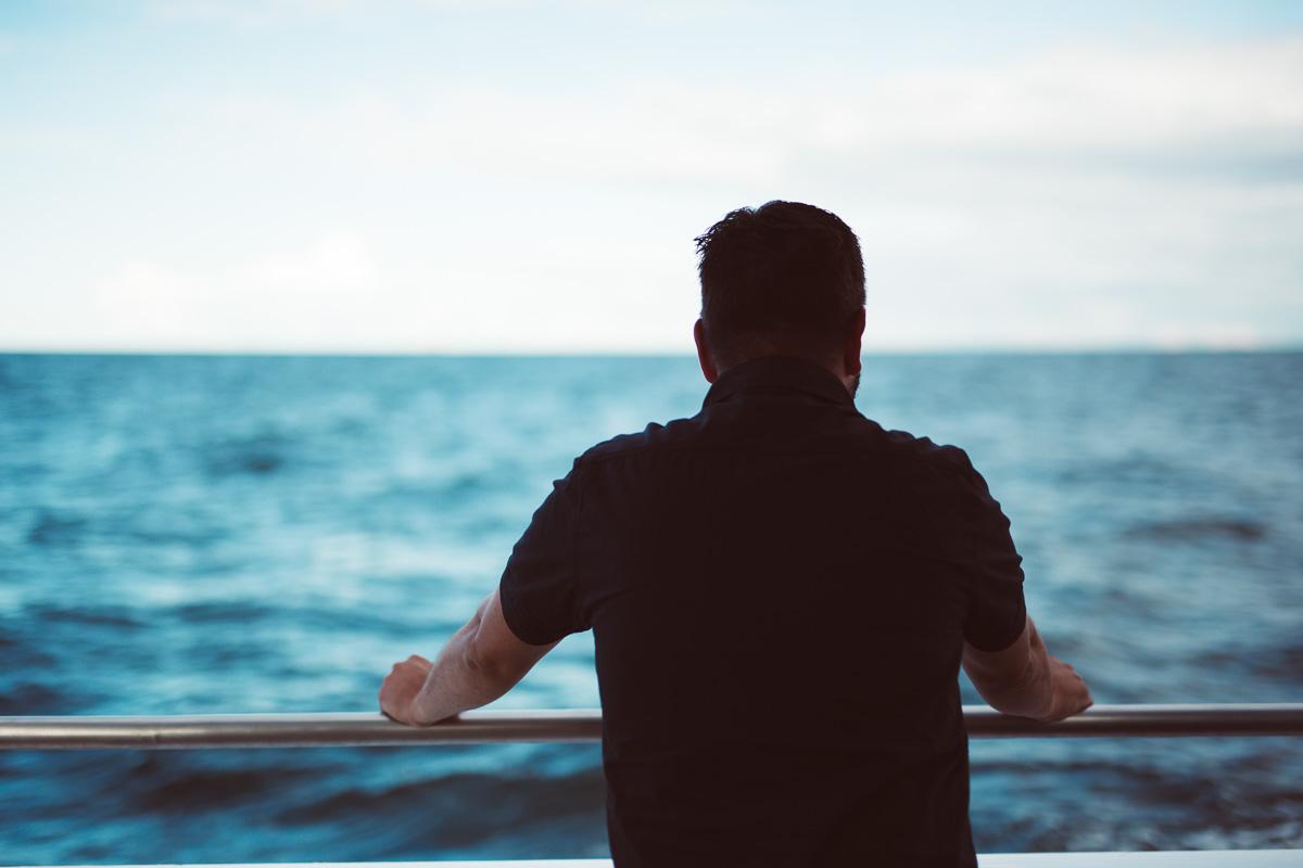 Mann steht am Bootsrand und schaut aufs Meer