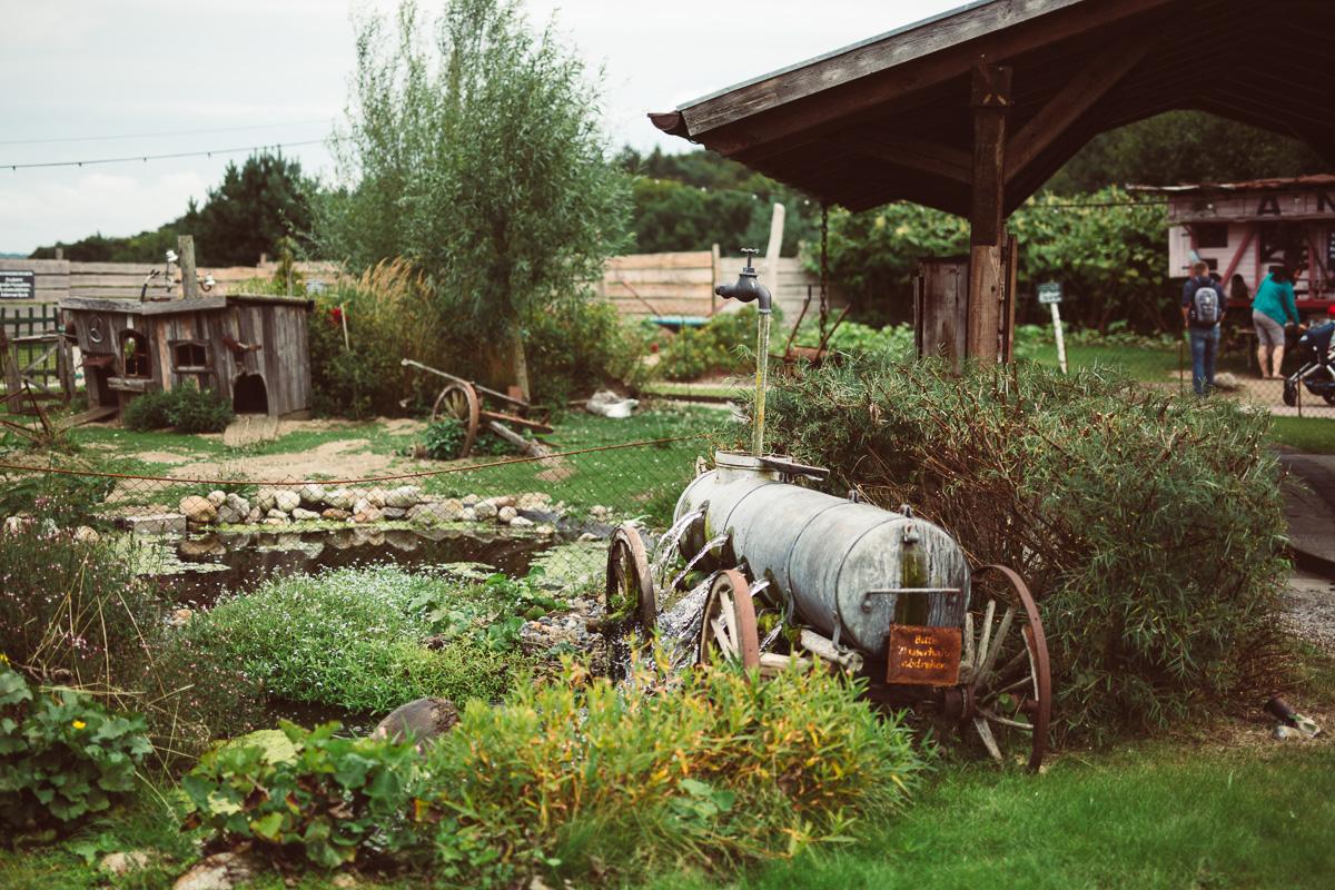 Wasserfass mit Löchern als Gartensprenger