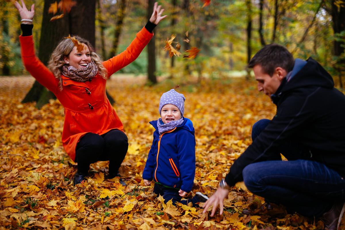 Familie mit Kind spielt im Laub