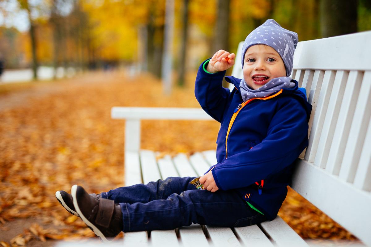 Kind sitzt auf einer Bank