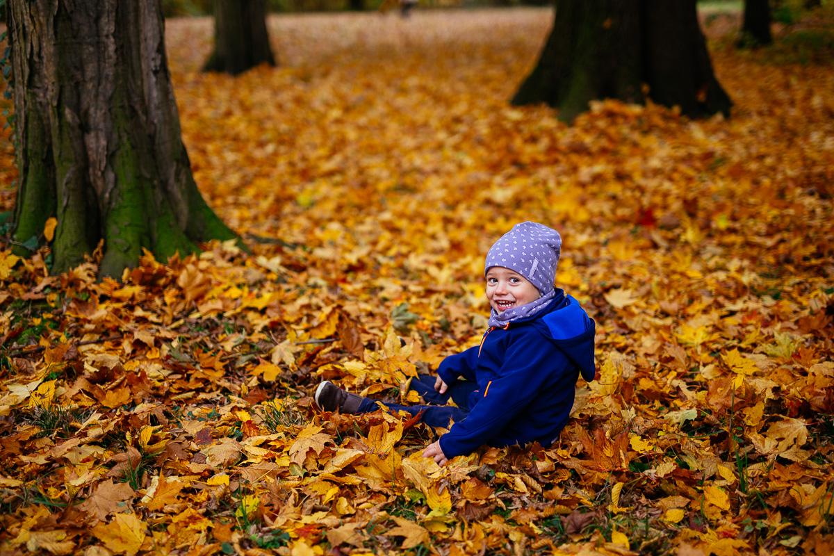 Kind sitzt im Laub