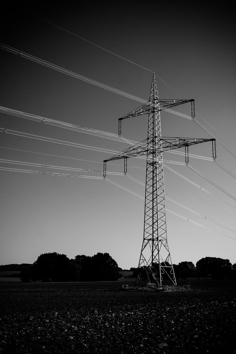Strommast auf einem Feld bei Uhyst in Schwarzweiss