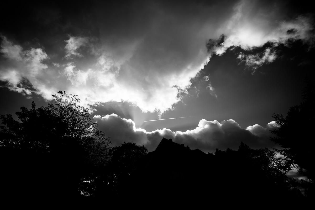 Ein Flugzeug mit Kondensstreifen fliegt durch eine Wolkenlücke und wird von der Sonne angestrahlt