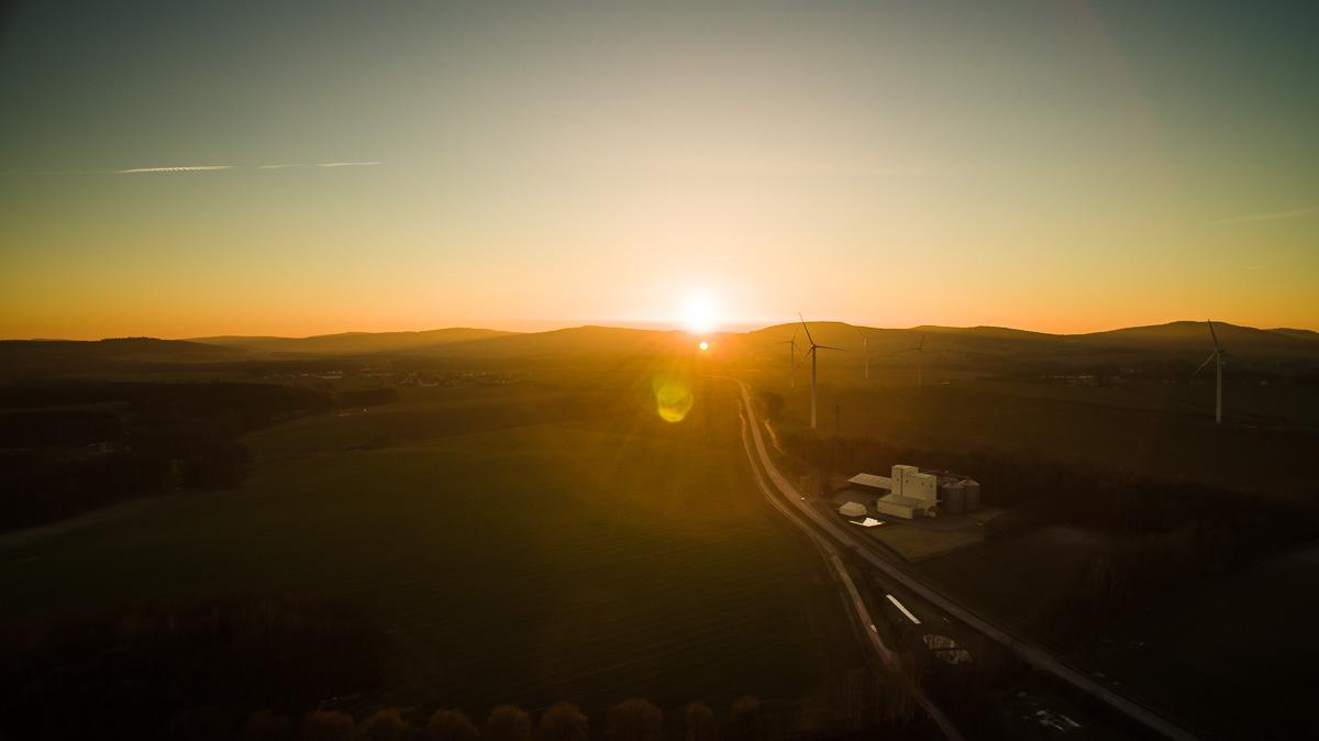 Sonnenuntergang und Windräder im Vordergrund