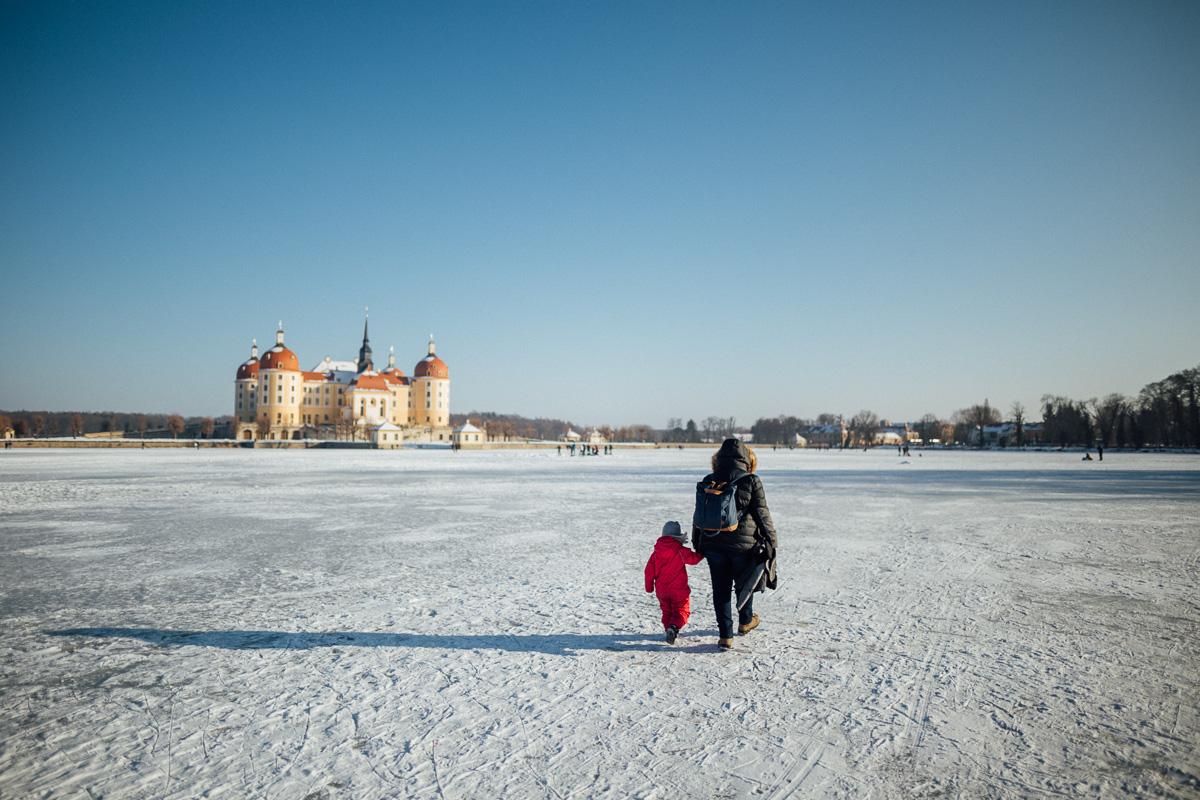 Mutter und Tochter wandern über den gefrohrenen Schlossteich von Schloss Moritzburg