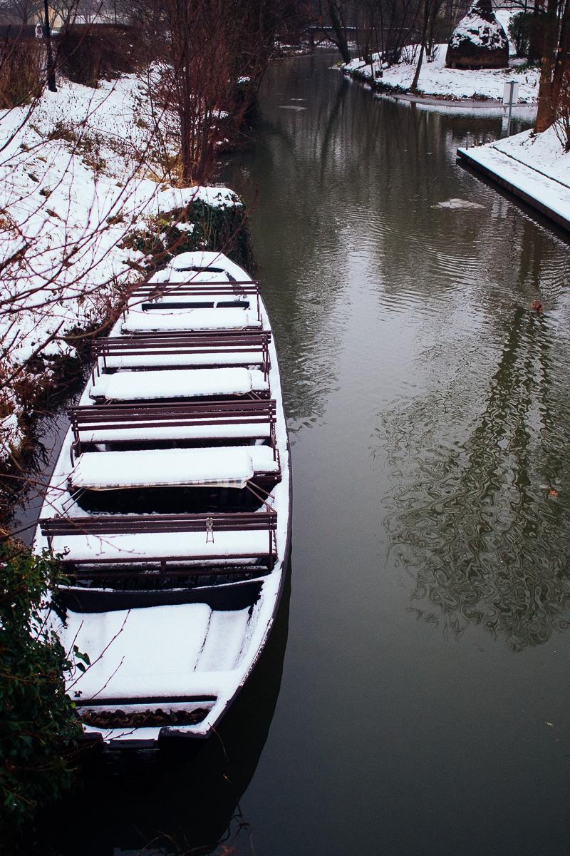 Ein Spreewald Kahn liegt schneebedeckt in einem Spreewaldkanal