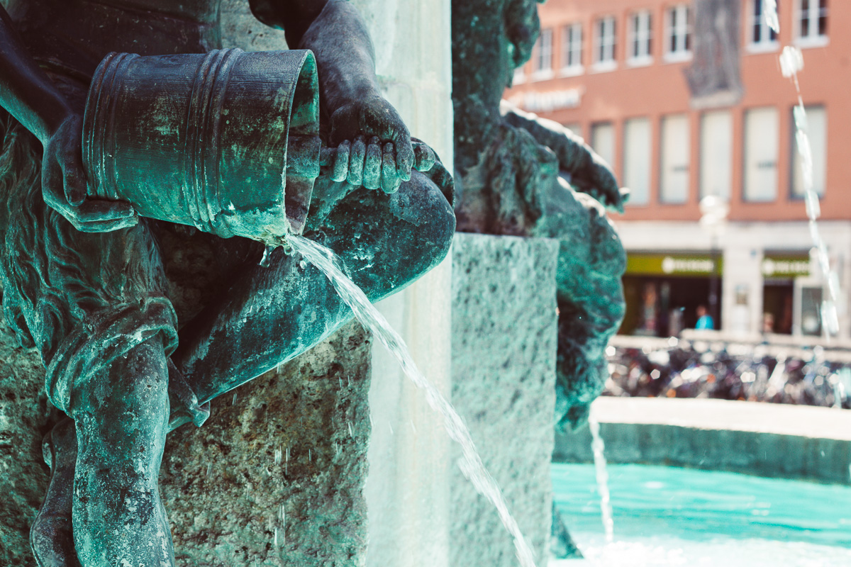 Eine Brunnenfigur mit einem Eimer am Marienplatz in München