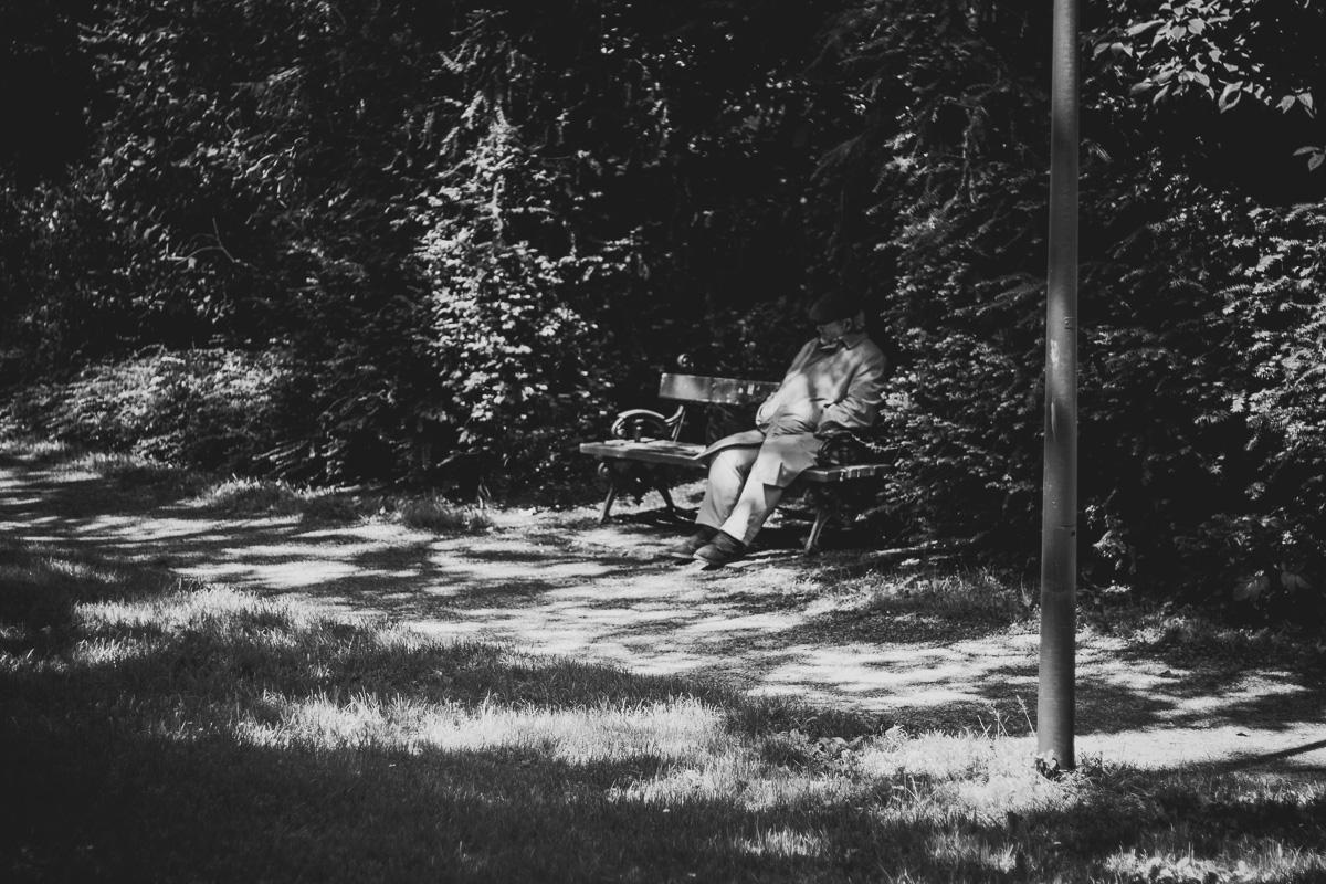 Ein Mann sitzt auf einer Bank und macht ein Nickerchen in München