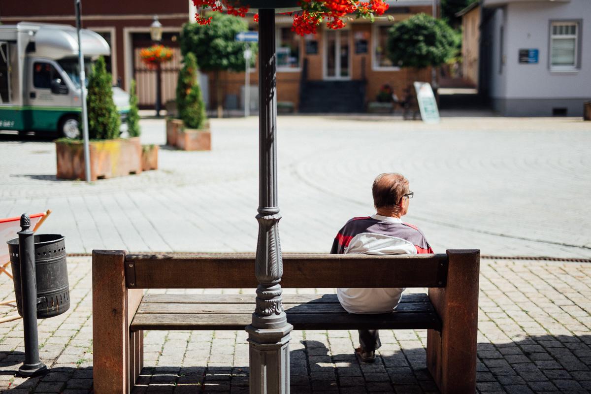 Ein Mann sitzt auf einer Bank auf dem Marktplatz in Schmölln