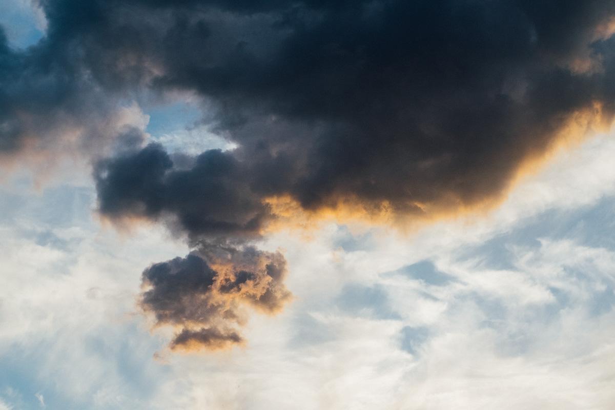 Dunkle Wolken werden am Hainer See bei Leipzig von der Abendsonne angestrahlt